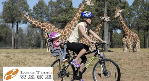 Mother and daugher on bike riding past giraffes at Taronga Western Plains Zoo Dubbo