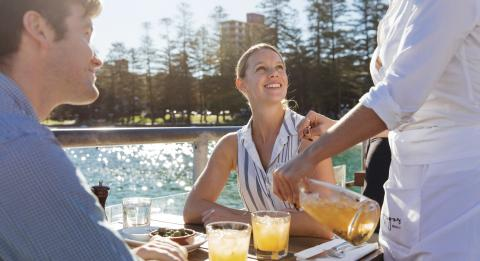 Couple enjoying food and drinks at Hugos Manly at Manly Wharf